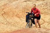 Girl pushing bicycle
