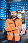 Worker in a forwarding company with his forklift looking into the camera poster