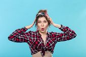 Beautiful Cheerful Young Pin-up Girl Posing In A Plaid Shirt And Bandage Against A Blue Background.  poster