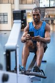 Front view of African-american Fit man using mobile phone while exercising on rowing machine in fitn poster