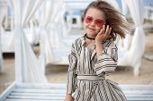 Small (8 Years Old) Pretty Cheerful Girl In A White Striped Dress And In Pink Sunglasses Stands On A poster