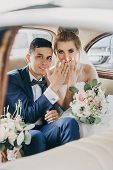 Just Married. Stylish Happy Bride And Groom Showing Hands With Wedding Rings, Sitting Inside Of Old poster