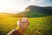 Male Hand With A Magnetic Compass Ea Against The Backdrop Of A Beautiful Landscape At Sunset. The Co poster