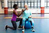 Side view of African-american Female trainer assisting disabled Caucasian senior woman to exercise w poster