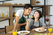 Cute Happy Couple In Aporn Having Breakfast Having Salad In Modern Kitchen And Having A Good Time poster