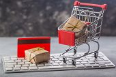 Christmas Or New Year Gift Paper Box Gold Ribbon In A Small Shopping Cart On A Laptop Keyboard. Conc poster