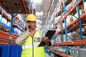 Front view of female worker looking at clipboard while talking on mobile phone in warehouse. This is poster