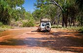 Western Australia – Flooded Outback gravel road with 4WD car crossing the waterhole at the savanna poster