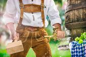 Bavarian man in leather trousers taps a wooden barrel of beer in the garden. Background for Oktoberf poster