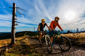 Cycling woman and men riding on bikes at sunset mountains forest landscape. Couple cycling MTB endur poster