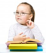 Cute little girl with books and glasses holding hand near her ear like listening to something, isola
