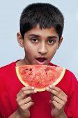 an handsome indian kid savoring a watermelon, a healthy diet