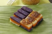 stock photo of ube  - Glutinous rice cake with different flavor per layer on banana leaf - JPG