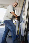 Portrait of a mechanic using jack lifter at garage