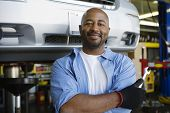 Portrait of a confident African American male mechanic holding wrench at garage