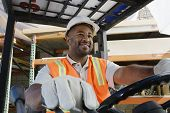 A happy  male industrial worker driving forklift at workplace