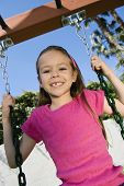 Portrait of a happy young girl swaying on a swing in the garden
