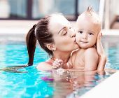 beautiful young brunette woman with her one year old baby relaxing in the swimming pool