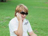 Menino loiro bonito e alegre em óculos de sol falando no telefone celular
