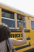 Rear view of mother waving goodbye to daughter in school bus
