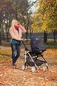 Young mother talking on a mobile phone during a walk in the park with her baby in a pushchair