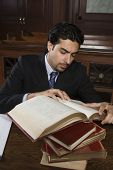 Male advocate taking reference from book while sitting in courtroom