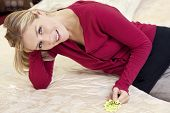 Happy young woman reclining on mattress with price tag