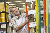 Portrait of a happy middle-aged man with ladder in hardware store
