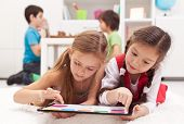 stock photo of indoor games  - Little girls playing on a tablet computing device  - JPG