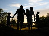 stock photo of holding hands  - silhouette of a family holding hands at sunset - JPG