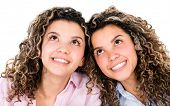 Thoughtful twins smiling and looking up - isolated over white background