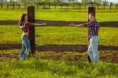 couple on the farm stading near fence