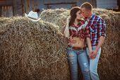 couple embracing near hay