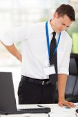 businessman having lower back pain in office