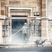 Worker Cleaning The Facade Of A Building