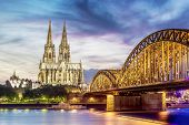 stock photo of koln  - Illuminated Dom in Cologne with bridge and rhine at sunset - JPG