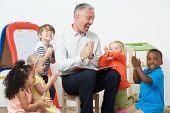 Pre School Teacher Reading Story To Children And Praying