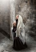 stock photo of verbs  - Jesus kneel in prayer toward the light - JPG
