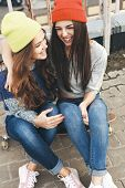 image of skate board  - Two young happy funky girl friends sitting together on longboard and having fun - JPG