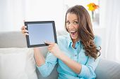 Euphoric woman showing her tablet screen sitting on cosy sofa