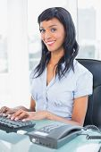 Cheerful businesswoman typing on a keyboard in office