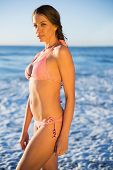 Attractive woman in pink bikini posing on the beach at dusk looking at camera