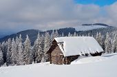 Winter landscape with a hut under the snow in a mountain valley. Carpathian mountains, Ukraine