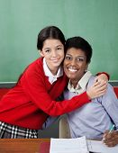 Portrait of little schoolgirl hugging female teacher at desk in classroom
