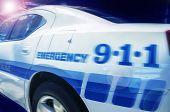 stock photo of chase  - 911 Emergency response police car speeding to scene of crime - JPG