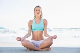 stock photo of slender  - Relaxed slender blonde in sportswear meditating on a sunny beach - JPG