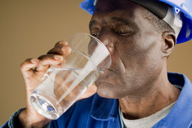 stock photo of drinking water  - Tired African American Construction Worker Drinking Water - JPG
