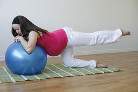 stock photo of pregnancy exercises  - A young pregnant woman in a pink shirt doing a buttock and leg muscle exercise using a blue fitness ball - JPG