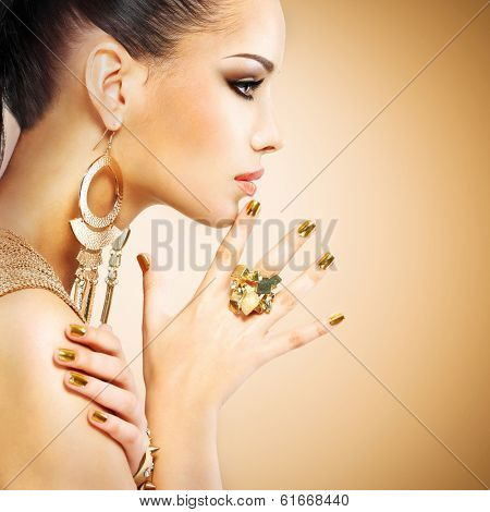 Profile portrait of the beautiful fashion woman with black makeup and golden manicure poster