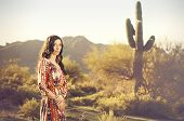 Beautiful young woman posing in desert landscape evoking positive wellbeing freedom lifestyle.